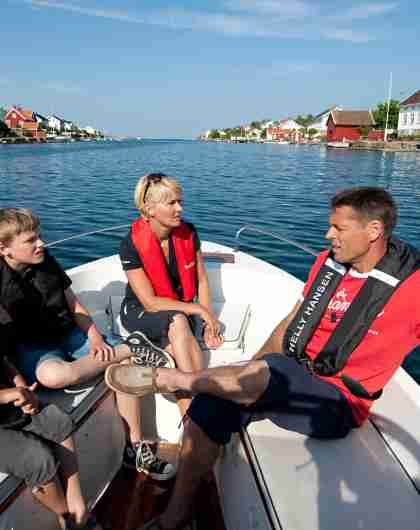 A family with life jackets in a boat on a summer day in Lyngør