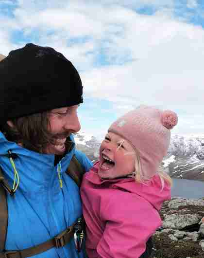 Close-up image of a young girl and her father smiling at each other on a hiking trip in Hjørundfjorden, Fjord Norway