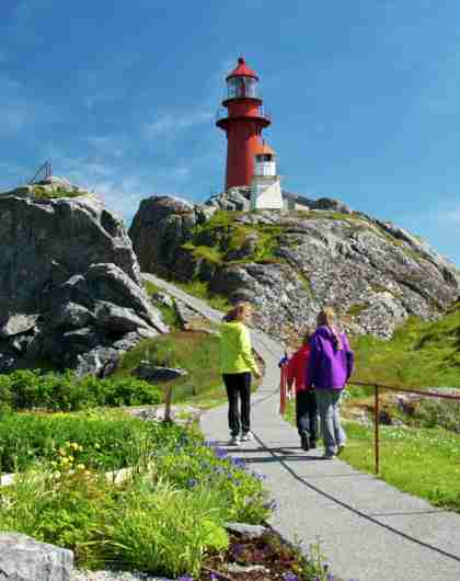 People walking towards Ona lighthouse in Møre og Romsdal, Norway