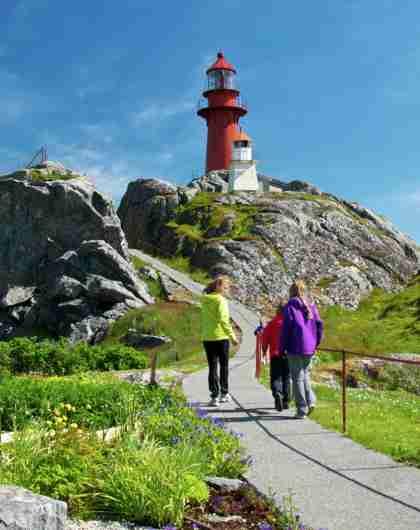 En familie går mot Ona fyr i Møre og Romsdal