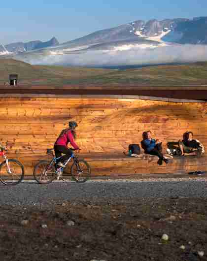 Two people cycling past viewpoint Snøhetta in Dovrefjell-Sunndalsfjella national park