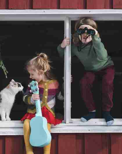 Two children are sitting in the window of their house, one of them holding a guitar and petting their cat, while the other is looking out through a pair of binoculars.