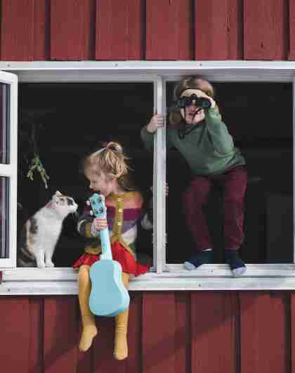 Two children are sitting in the window of their house, one holding a guitar and petting their cat while the other is looking through binoculars.
