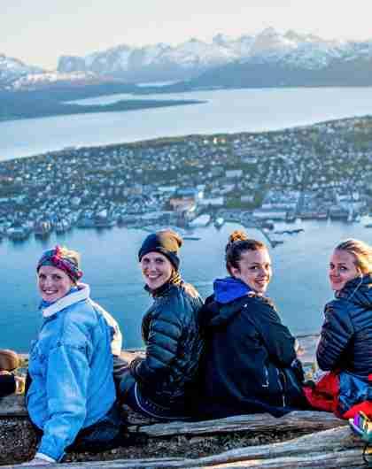 En gruppe jenter sitter og nyter utsikten over Tromsø by