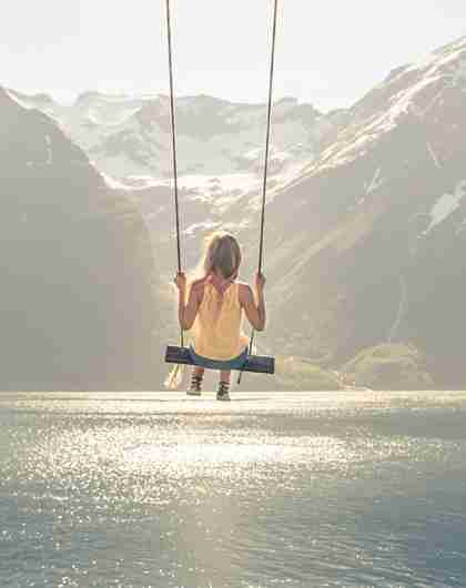 A girl on a the world's most beautiful swing in Trandal by the Hjørundfjord in Fjord Norway