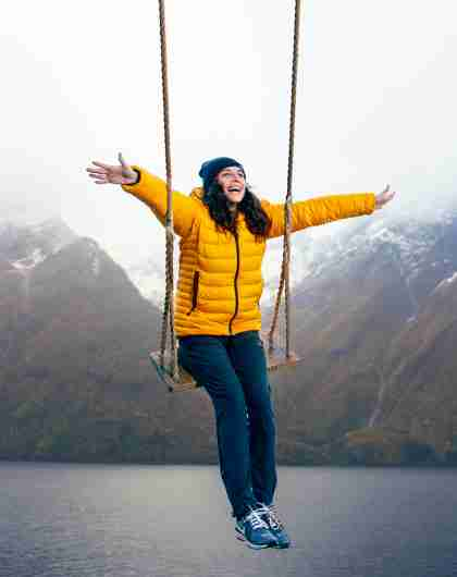 A person on a swing with views of snow-clad mountains and the Hjørundfjord in Fjord Norway