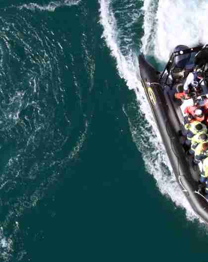 A RIB filled with people seen from above on Saltstraumen in Bodø, Northern Norway