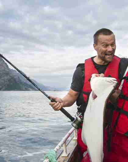 To menn fisker fra en båt i Tromsø