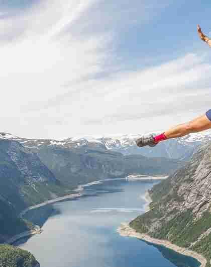 En jente klatrer Trolltunga via ferrata på en solskinnsdag i Hardanger på Vestlandet