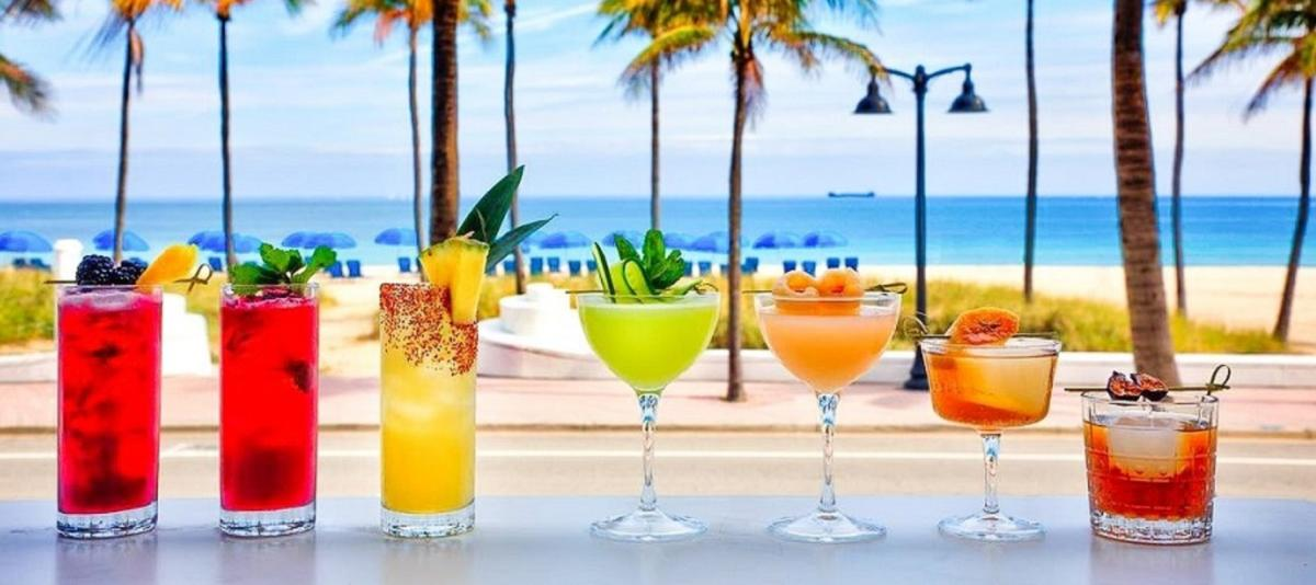 A selection of 7 craft cocktails on a counter with the ocean in the background