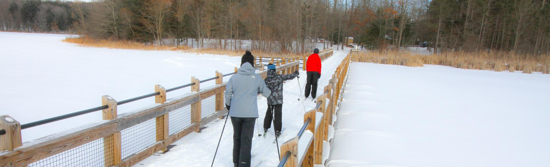 A family crossing the bridge while cross country skiing at Pickerel Lake.