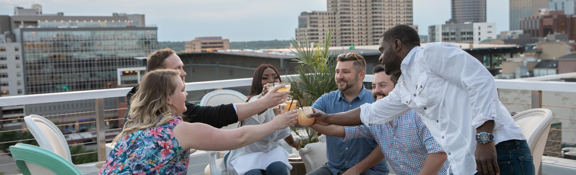 Friends enjoying cocktails and cheers-ing on rooftop
