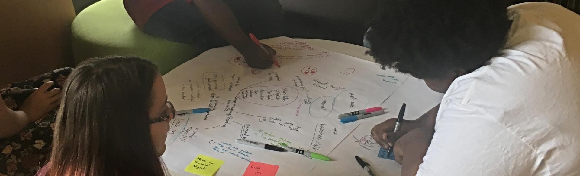 Teens working together with pen and paper on a table