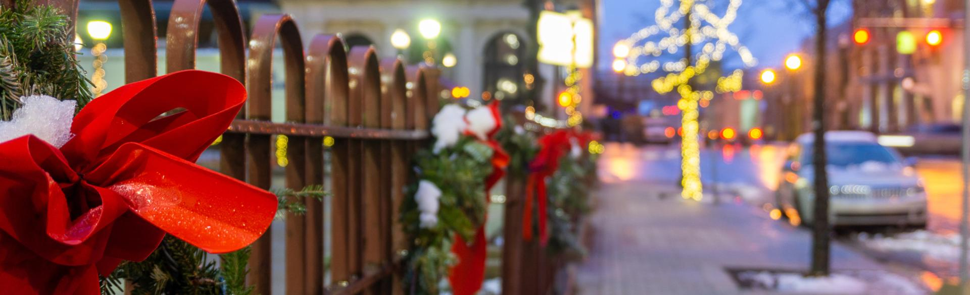 Fence decorated with bows and garland for the holidays.
