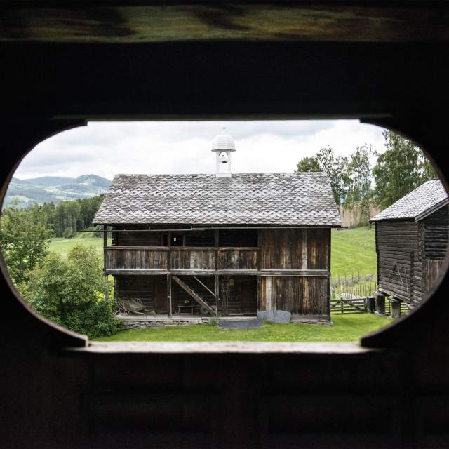 View on a wooden shed through a hole in the wooden wall at Sygard Grytting