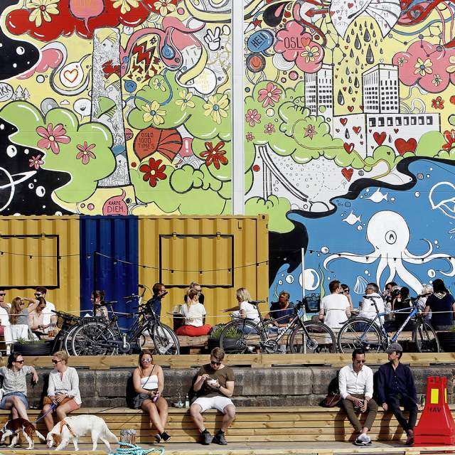 People sitting in front of a wall with street art at Vippa food court in Oslo, Norway
