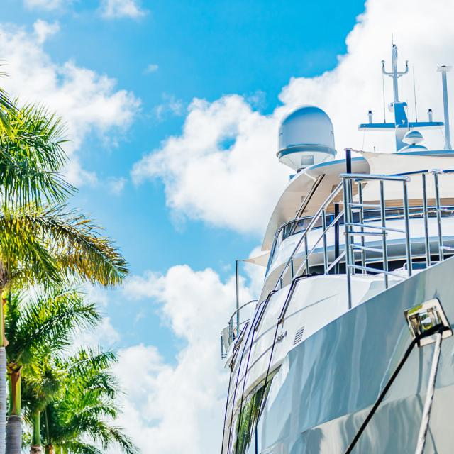 Mega-yacht next to palm trees with fluffy white clouds floating in a clear blue sky