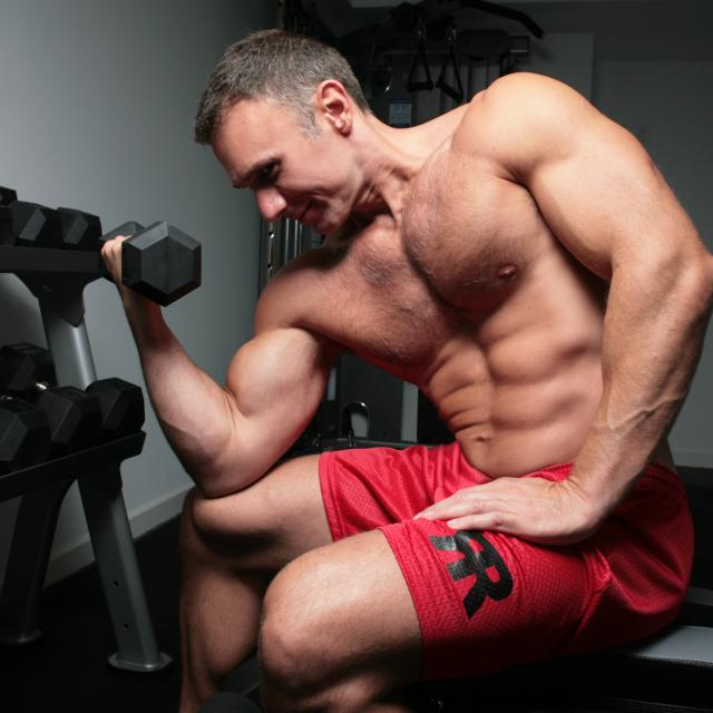 Shirtless, very fit man doing bicep curls