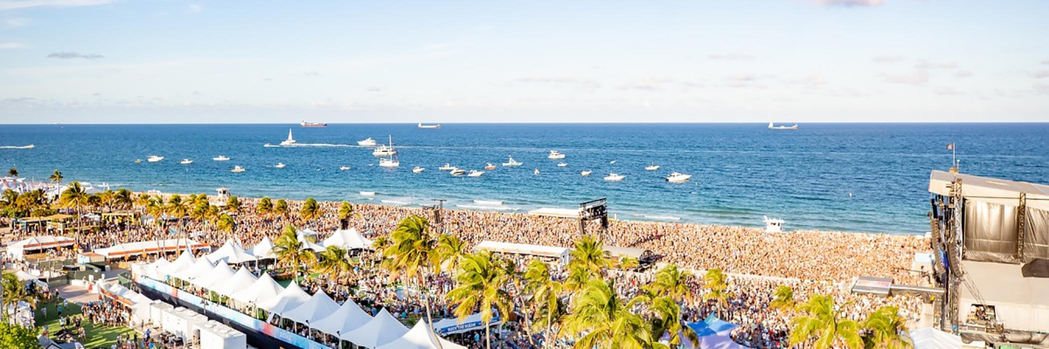 Aerial photo of crowds of listeners on Fort Lauderdale Beach with boats anchored in the waters off-shore