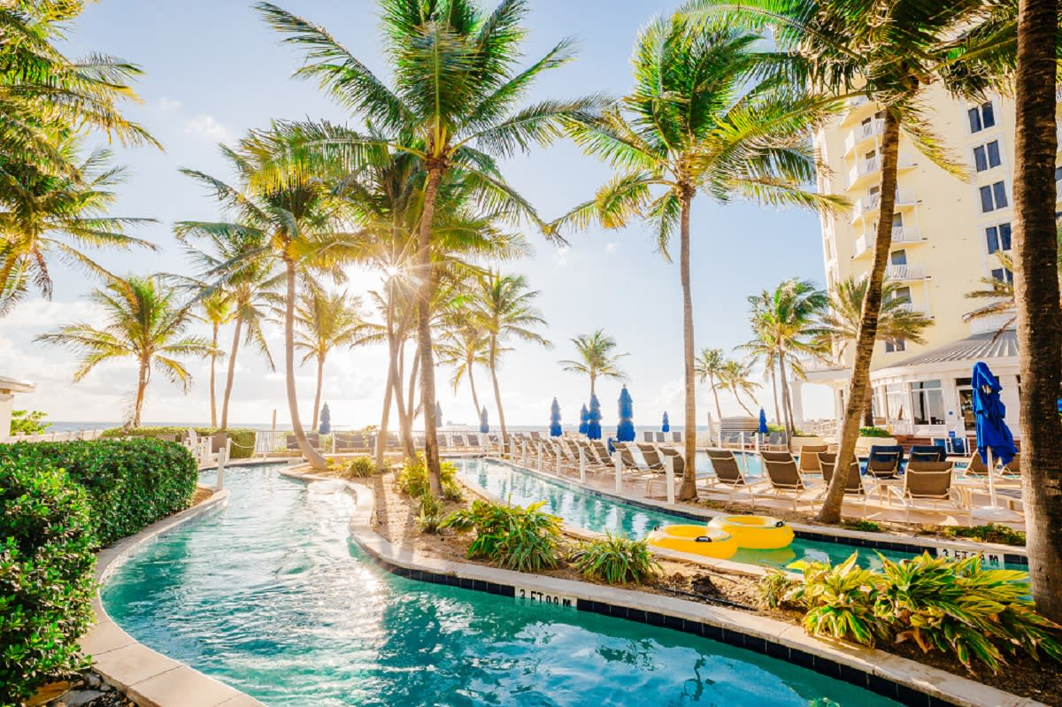 Lazy River at the Pelican Grand Resort on a sunny day with palm trees and a bright blue sky
