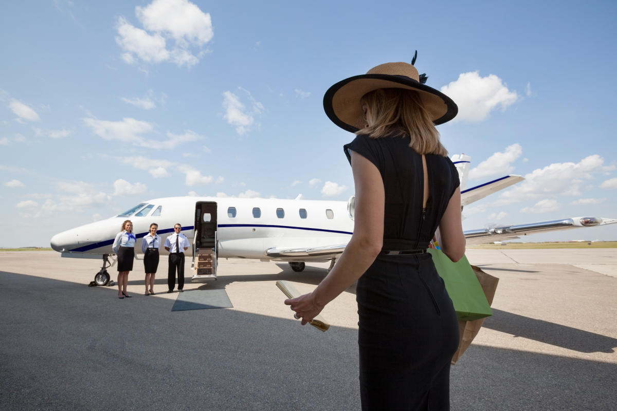 Woman in a black dress and sun hat walking toward a private jet, ready to board