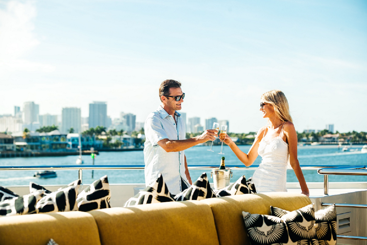 A couple on the deck of a yacht toasting with champagne