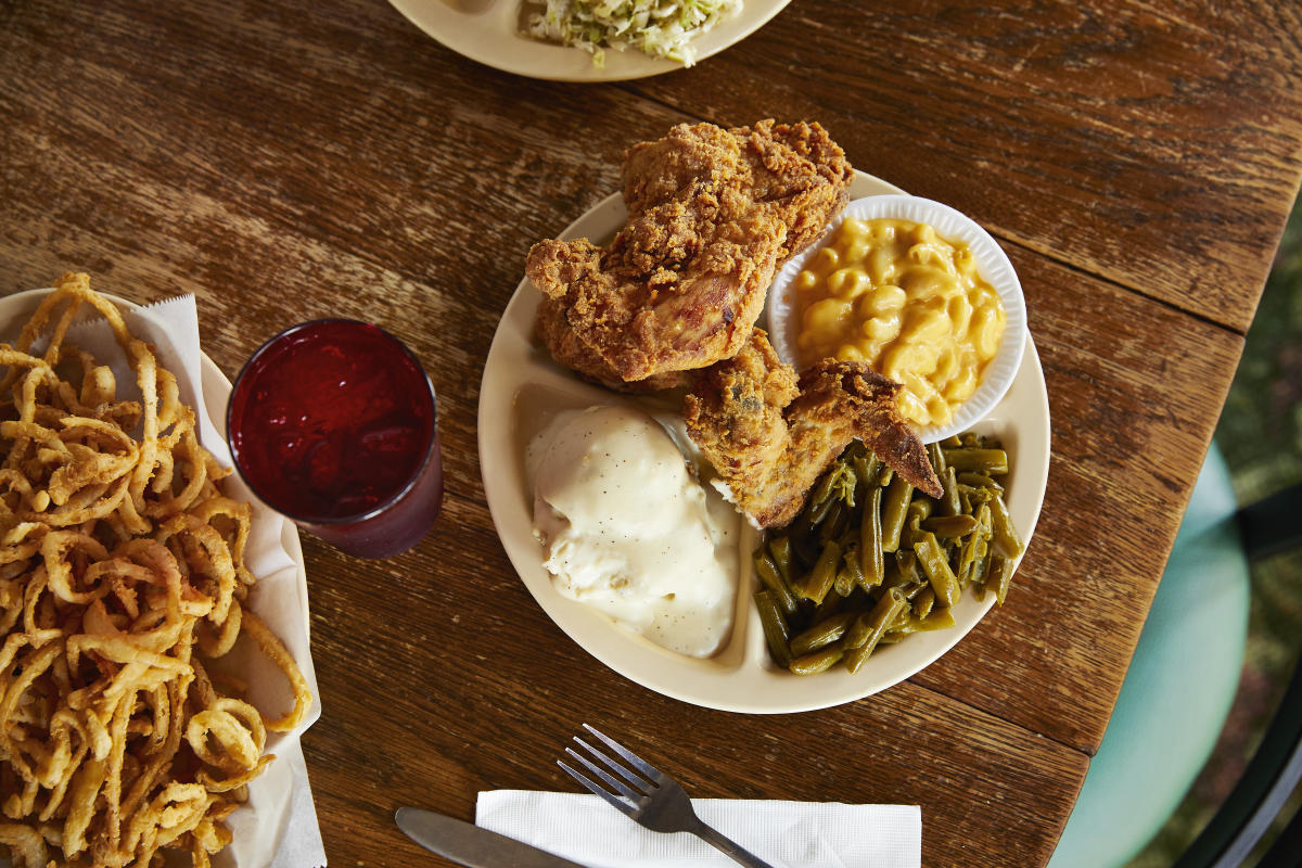 Fried chicken, mashed potatoes, mac and cheese and green beans served on a plate at Chicken Mary's