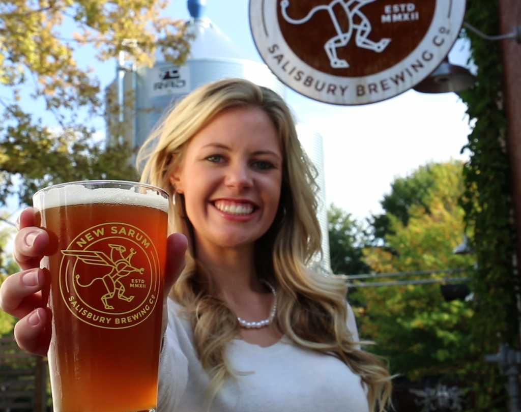 Woman holding glass of New Sarum Beer
