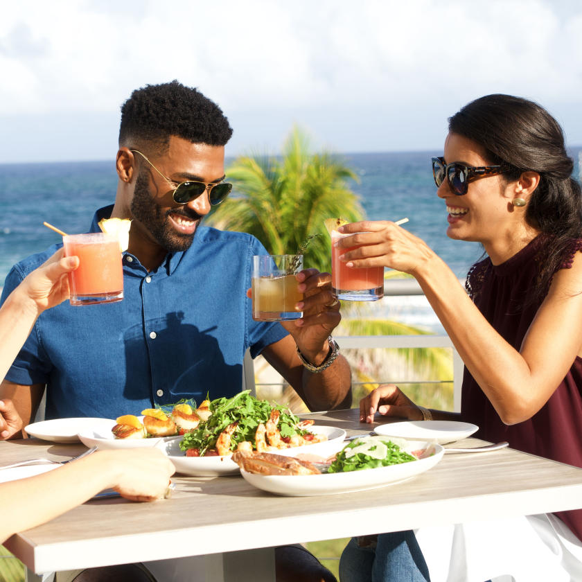 People holding up their glasses while dining on a patio in Fort Lauderdale