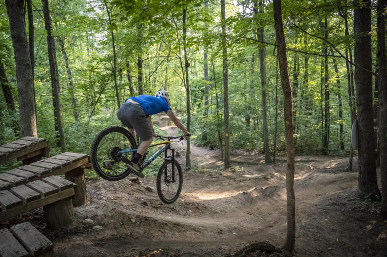 Mountain biker jumping off a platform on  a trail near Grand Rapids