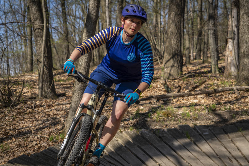 Mountain biker in blue shirt with stripes biking on a trail near Grand Rapids