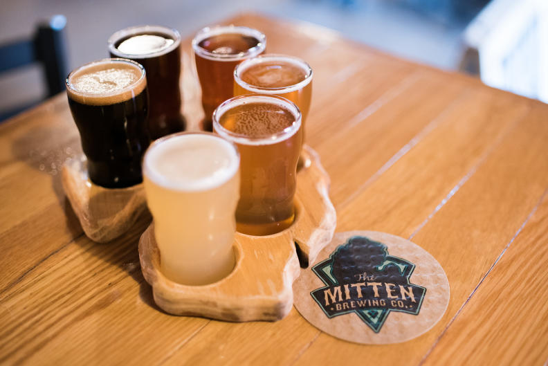 Grab a mitten-shaped beer flight to go with your pizza flight at The Mitten Brewing Co.