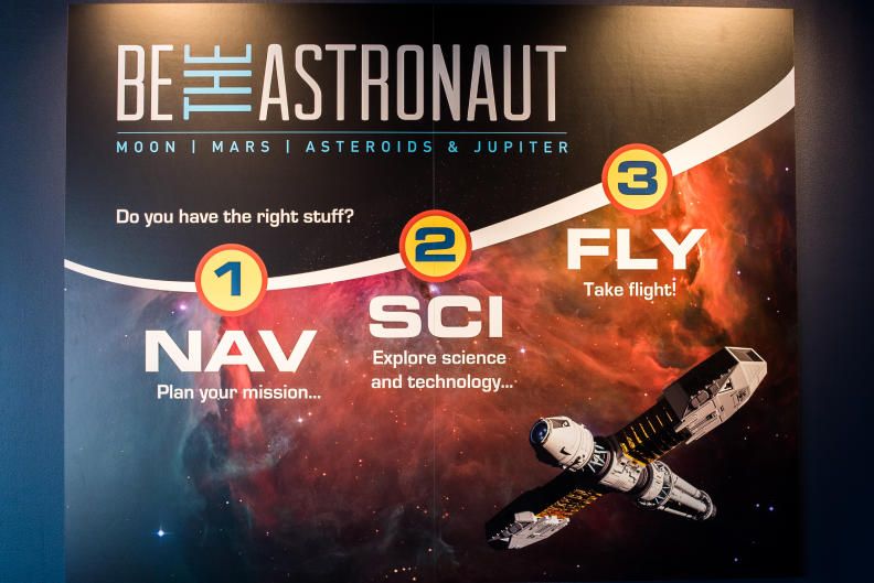 The Be the Astronaut exhibit is split into three categories: Nav - Plan your mission, Sci - Explore science and technology, and Fly - Take flight!