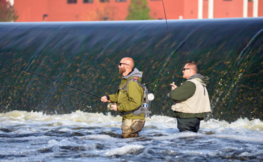 Two area angler wade-fish for steelhead on the Grand River just downstream from the Sixth Street Dam on the east side of the river