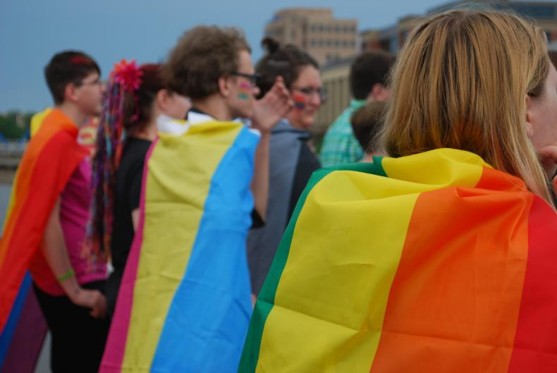 Several Pride Festival Attendees in Grand Rapids wearing Pride Flags as capes