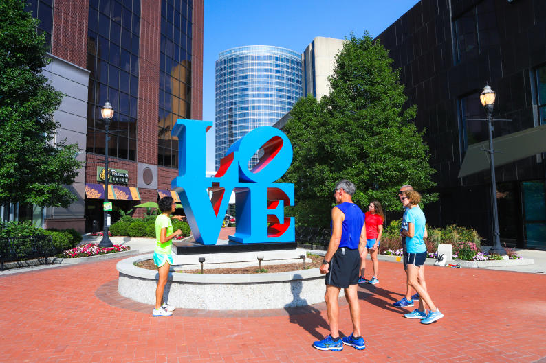 A running tour stops to admire LOVE by Robert Indiana.