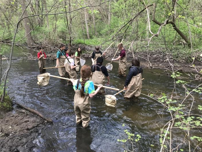 Grand Rapids students volunteers cleaning up a river