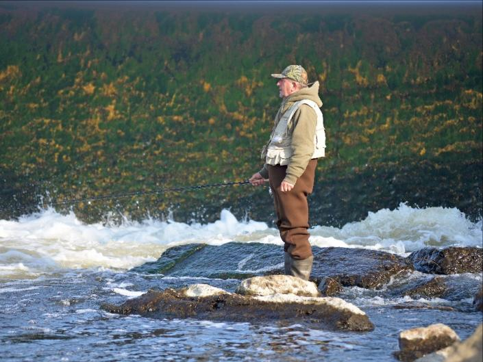 An angler fishes from the rocks immediately downstream of the Sixth St. Dam