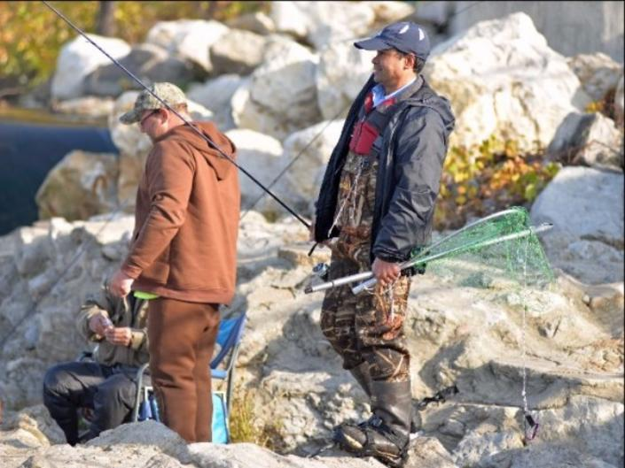 Anglers often gather along the river bank at the Sixth St. Dam where they swap stories and watch each other fish