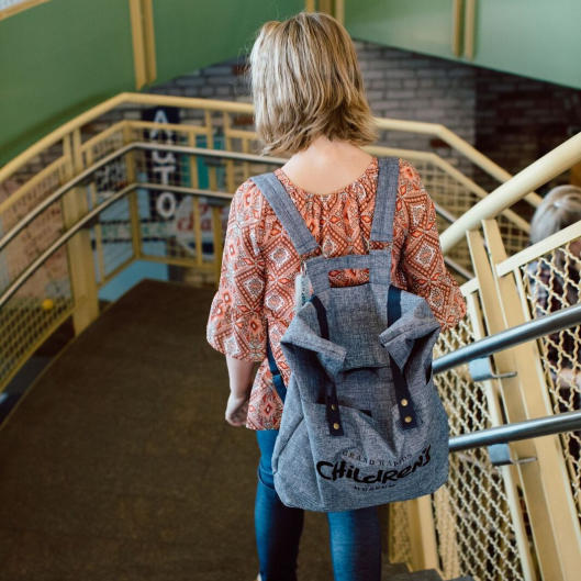 Child with backpack walking down stairs at the Grand Rapids Children's Museum