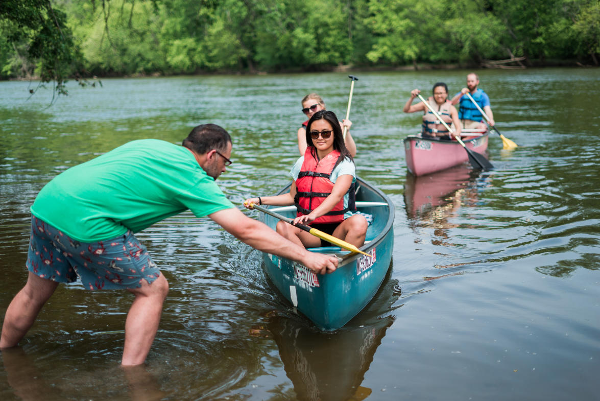 Matt Clouse, owner of Grand River Kayak and Canoe, helps paddlers out of the water from their Grand River canoe trip.